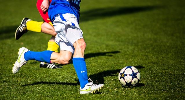 Fussball auf einem Rasen, sowie mehrere Beine von Fussballern daneben
